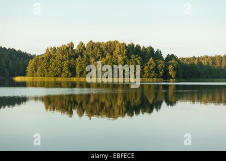 Landscape with trees and sky reflected in the lake - Stock Photo