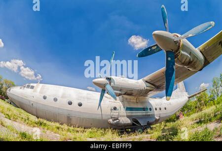 Old russian aircraft An-12 at an abandoned aerodrome - Stock Photo