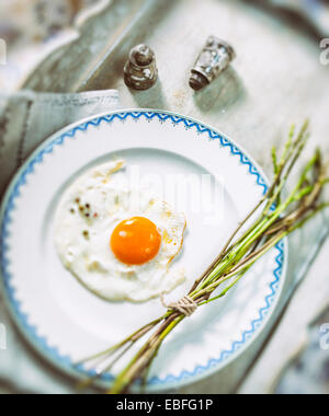 Fried egg and fresh wild asparagus on a white plate - Stock Photo