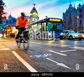 Cyclist at the cycle lane of Alcal‡ street with the Metropolis building at the background. Madrid, Spain. - Stock Photo