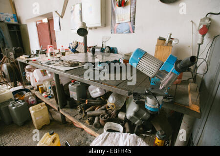 Messy car garage with various tools - Stock Photo
