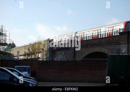 London Tube train approaching Latimer Road tube station with trains running overground amongst the buildings. - Stock Photo