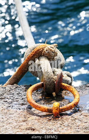 Ropes on a iron mooring ring. Shallow depth of field. - Stock Photo