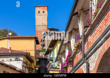 Small italian town and medieval tower under blue sky in Piedmont, Northern Italy. - Stock Photo