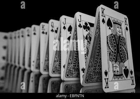 A set of playing cards in formation, reflecting onto the table below. - Stock Photo
