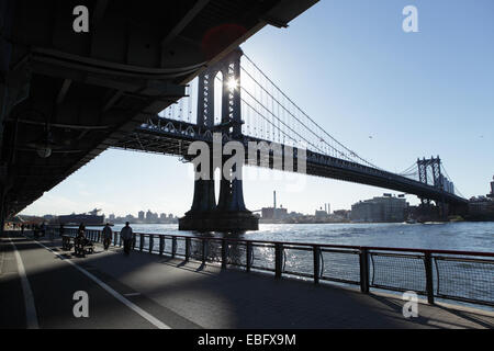 East River New York with the Manhattan Bridge in the background as the sun rises - Stock Photo