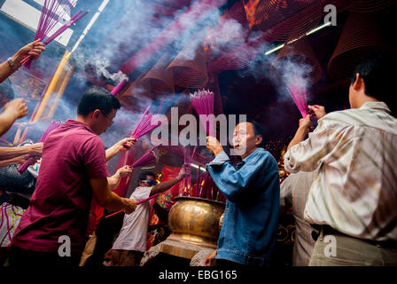 People burning joss sticks (incense sticks) during Chinese New Year celebration at Jin De Yuan temple, Jakarta, - Stock Photo