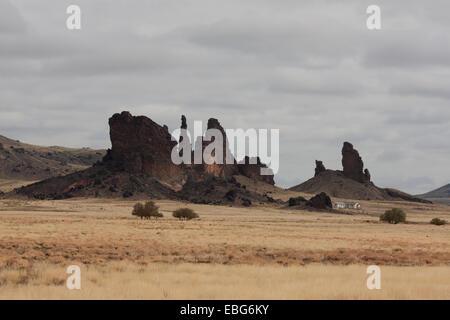 DWELLING NEAR SOME VOLCANIC DIKES. Dilkon, Navajo Land, Arizona, United States. - Stock Photo