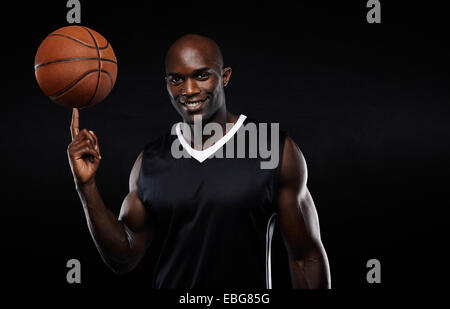 Portrait of happy young African athlete balancing basketball on his finger. Confident basketball player against - Stock Photo