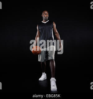 Full length portrait of young professional basketball player standing over black background. African young man in - Stock Photo