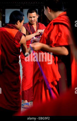 Buddhist monks producing textile trimmings, Trongsa, Trongsa District, Bhutan - Stock Photo