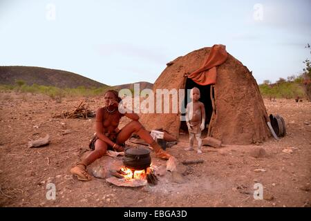 Young Himba woman cooking food on a campfire outside her hut, Ombombo, Kaokoland, Kunene, Namibia - Stock Photo