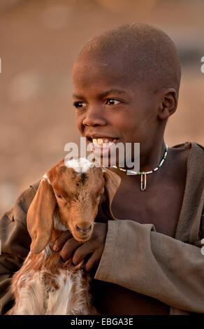 Himba boy with a goat, Ombombo, Kaokoland, Kunene, Namibia - Stock Photo