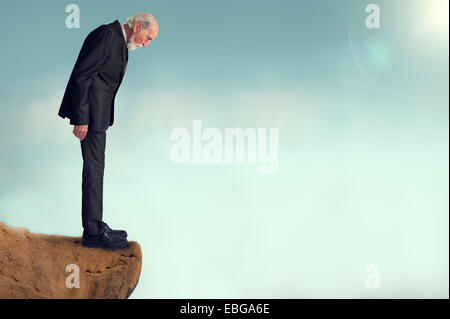 senior man looking down from a cliff - Stock Photo