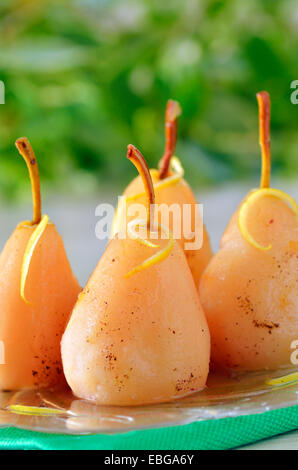 four pears poached in syrup - Stock Photo