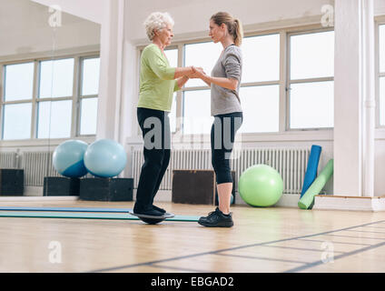 Female trainer helping senior woman standing on a balance board at gym. Elder woman exercising being assisted by - Stock Photo