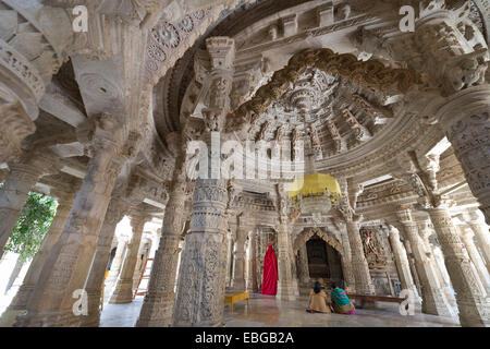 Women sitting in the Interior hall with ornate pillars and ceilings in the marble temple, Adinatha Temple - Stock Photo