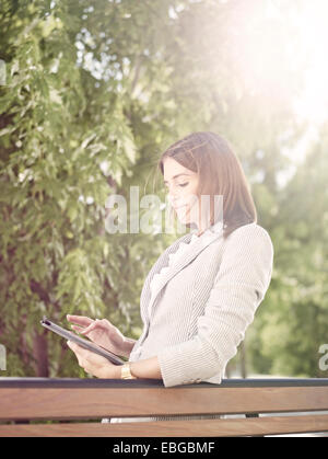 Woman wearing a business suit standing with a tablet computer behind a park bench, Innsbruck, Tyrol, Austria - Stock Photo