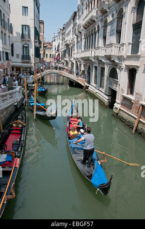 Bridge over canal Rio de la Canonica and gondalas with gondalier and sunshine Venice Italy - Stock Photo
