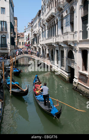 Bridge over canal Rio de la Canonica and gondalas with gondalier and sunshine Venice Italy - Stock Photo