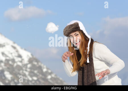 Playful woman throwing a snow ball in winter on holidays in a snowy mountain - Stock Photo