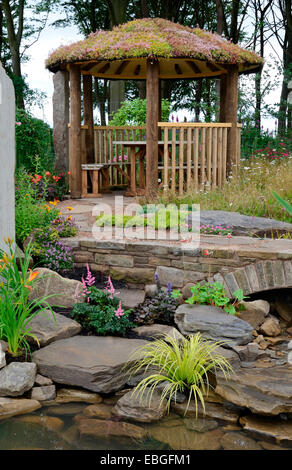 An attractive water garden with sandstone rock bridge and a wooden summerhouse with a Sedum roof - Stock Photo