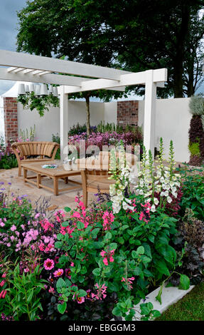 A contemporary garden with terraced area and stylish wooden furniture surrounded by colourful flowering borders - Stock Photo