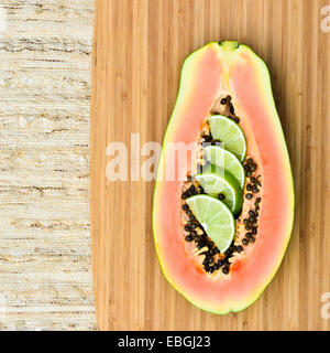 Fresh papaya cut in half on a wooden board