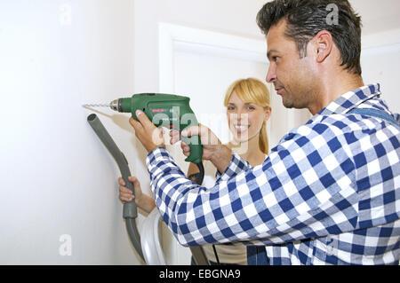 personen symbolfoto mann frau paar bohren wand staub staubsauger stockfoto lizenzfreies bild. Black Bedroom Furniture Sets. Home Design Ideas