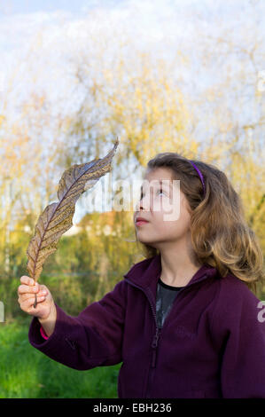 Young child holding a big Autumn Fall leaf in the park. - Stock Photo