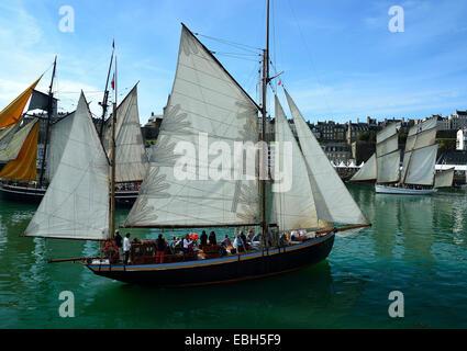 Classic yacht 'Lys noir'parade under sail into the port of Granville during a maritime event ('Voiles de travail'). - Stock Photo