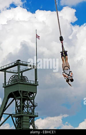 bungee jumping in front of a pit frame in Olga Park, Germany, North Rhine-Westphalia, Ruhr Area, Oberhausen - Stock Photo