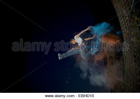 Parkour athlete experimenting with movement and powder paint at Balcombe Viaducts, Sussex, United Kingdom - Stock Photo