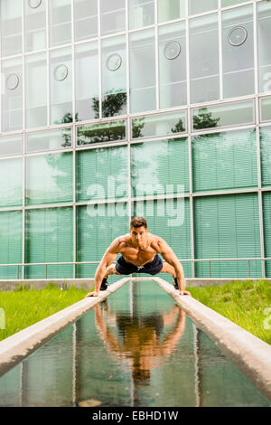 Personal trainer doing outdoor training in urban place, Munich, Bavaria, Germany - Stock Photo