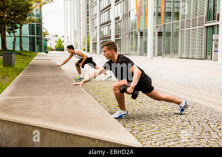 Personal trainers doing outdoor training in urban place, Munich, Bavaria, Germany - Stock Photo