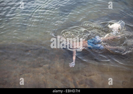 High angle view of teenage boy swimming underwater in Lake Superior, Au Train, Michigan, USA - Stock Photo