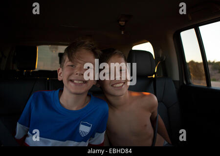 Portrait of brothers smiling in car back seat - Stock Photo