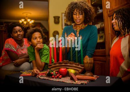 Family lighting kinara candles, celebrating Kwanzaa - Stock Photo