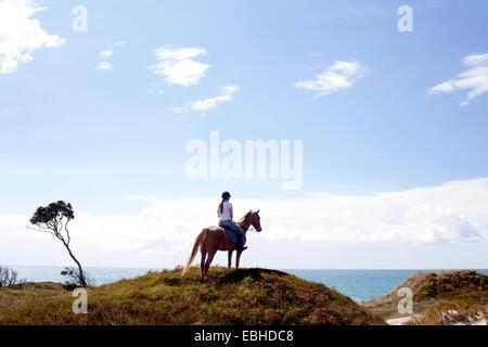 Horse rider on hilltop, Pakiri Beach, Auckland, New Zealand - Stock Photo