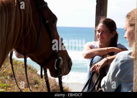 Horse riders taking break, Pakiri Beach, Auckland, New Zealand - Stock Photo