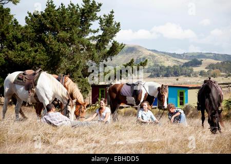 Horse riders taking break on grass, Pakiri Beach, Auckland, New Zealand - Stock Photo