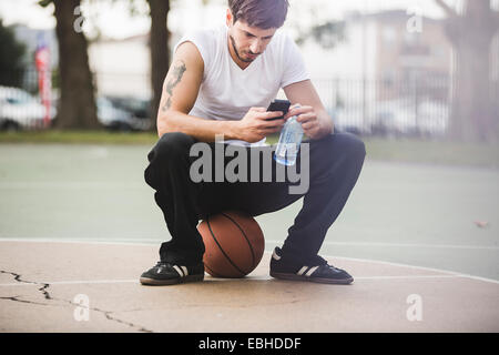 Young male basketball sitting on ball texting on smartphone - Stock Photo