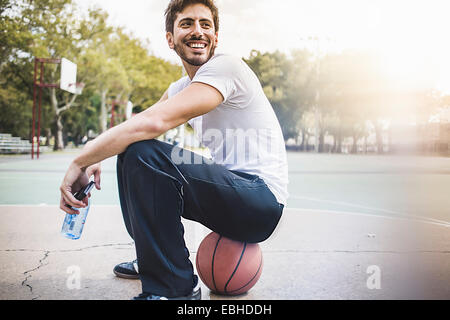 Portrait of young male basketball sitting on ball - Stock Photo