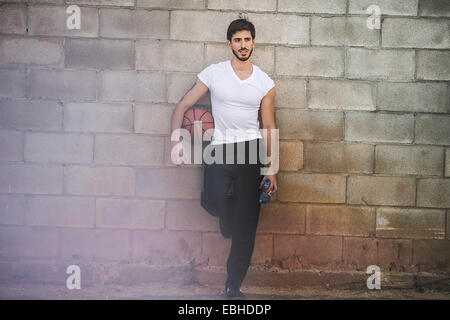 Young male basketball player leaning against wall - Stock Photo