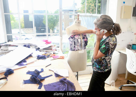 Designer on smartphone working in studio - Stock Photo