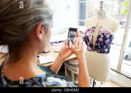 Designer taking photograph of her creation in studio - Stock Photo