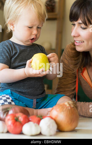 Young boy holding pear with mother - Stock Photo
