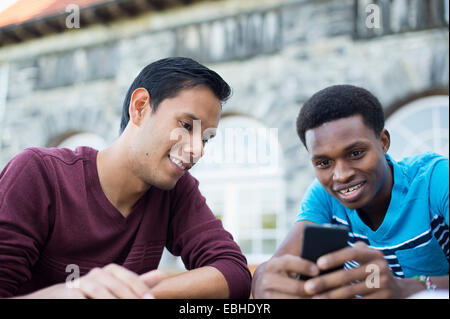Two male friends using smartphone - Stock Photo