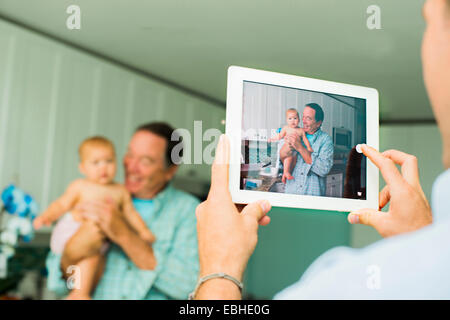 Over shoulder portrait of grandfather and baby granddaughter taken on digital tablet in living room - Stock Photo