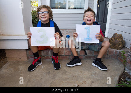 Portrait of two brothers sitting in porch holding up pieces of paper with 3 & 1 - Stock Photo
